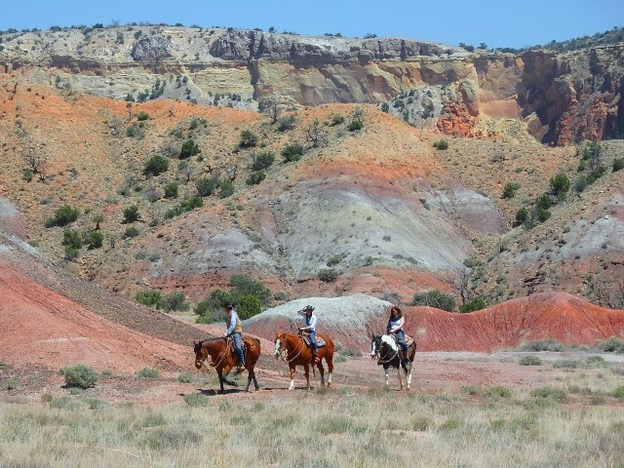 Ghost Ranch horse riders in red and yellow cliffs
